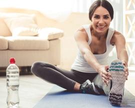 Femeie practicând gimnastică venoasă pe o saltea de yoga pentru a preveni senzaţia de greutate a picioarelor